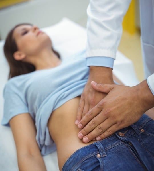 doctor examining the stomach of 3 showing the concept of About Us